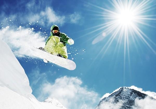 Snowboarder at jump inhigh mountains
