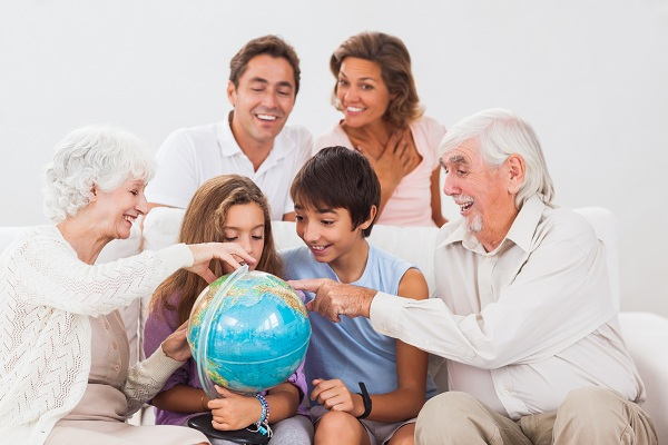 Extended family looking at globe on couch