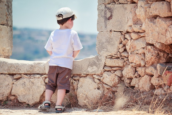 Back view of cute little boy outdoors in city