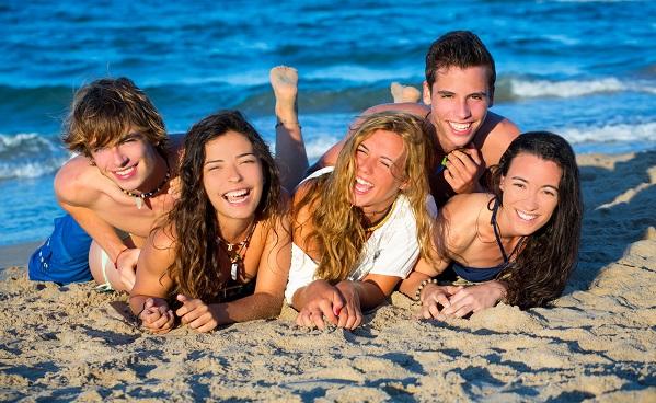 Boys and girls group having fun on the beach