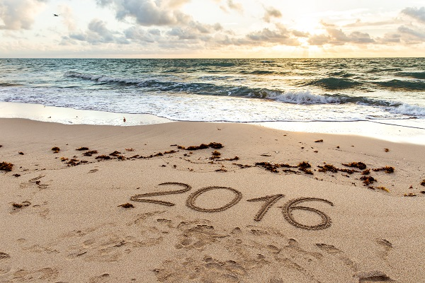Year 2016 written on sand at sunset