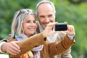 Cheerful senior couple taking picture with smartphone