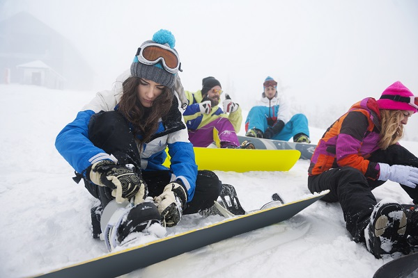 Women focused on clasping ski shoes