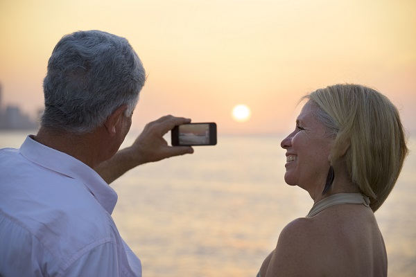 Senior man and woman using mobile phone to take photo