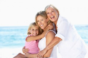 Grandmother With Daughter And Granddaughter Embracing On Beach H