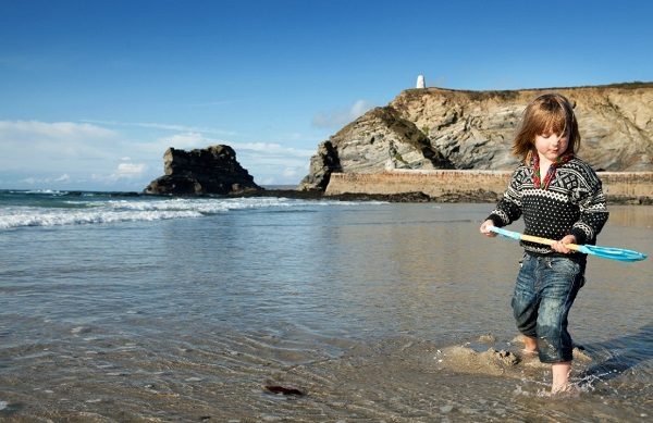 little girl with a spade, digging sand on a beach in Cornwall